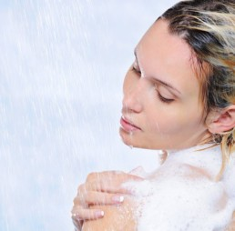 woman using ReTone exfoliating cleanser in the shower